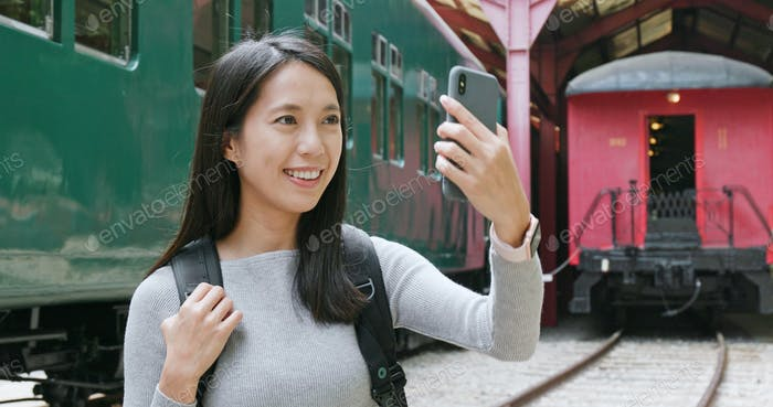 Woman taking photo by mobile phone on train station