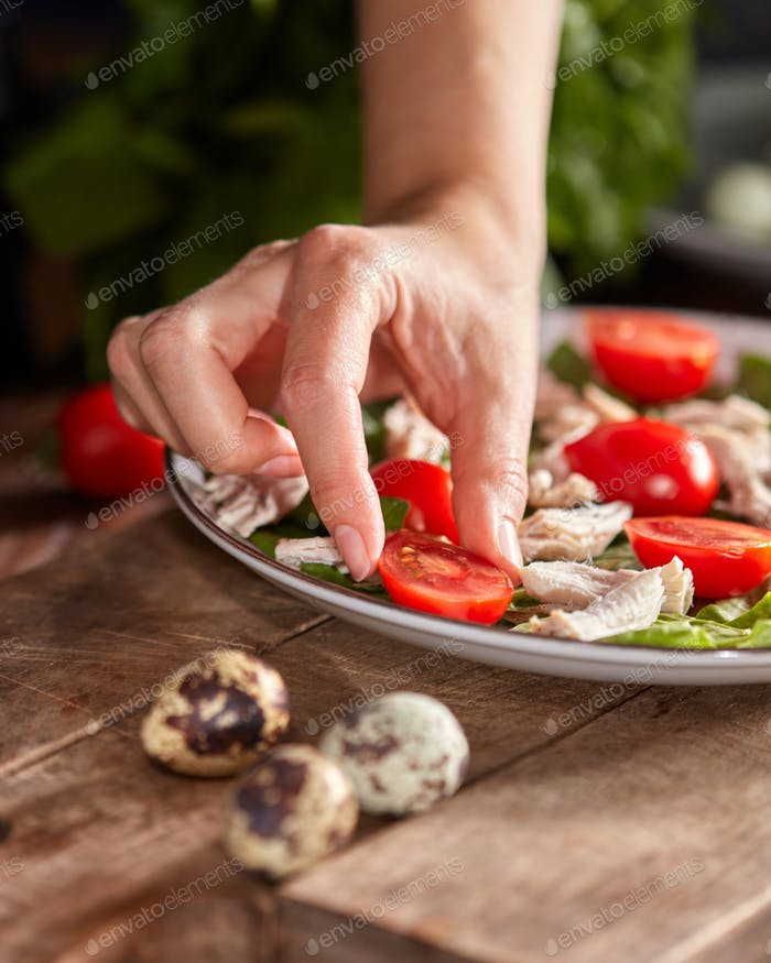 Woman hand put tomato cherry to a ceramic plate of fresh salad with organic ingredients on a wooden