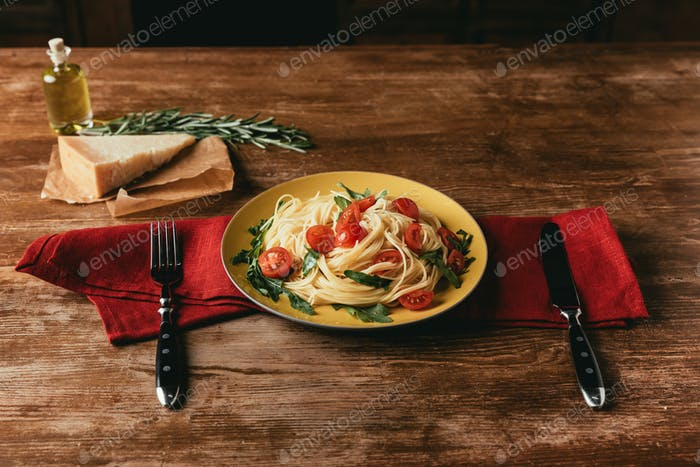traditional pasta with tomatoes and arugula in plate on table with Parmesan and rosemary
