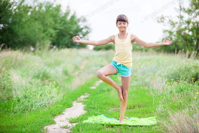 Little girl standing in tree yoga position