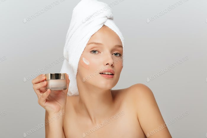 Portrait of young attractive lady with white towel on head witho