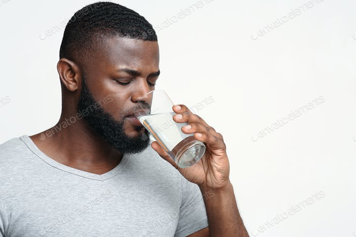 Young afro guy drinking water to be healthy