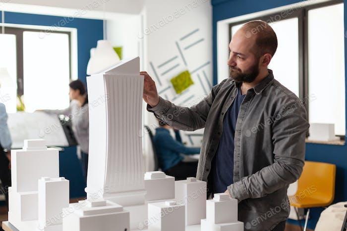 Hombre arquitecto mirando diseño en oficina profesional