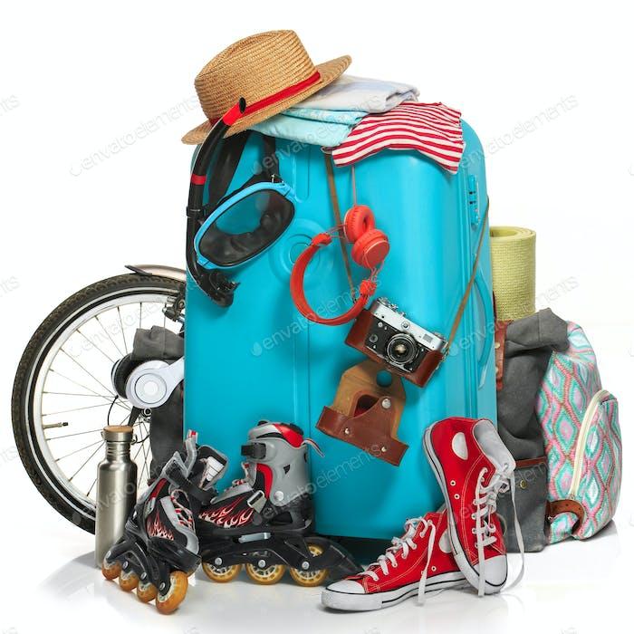 La maleta azul, zapatillas de deporte, ropa, sombrero y cámara Retro sobre Fondo blanco.