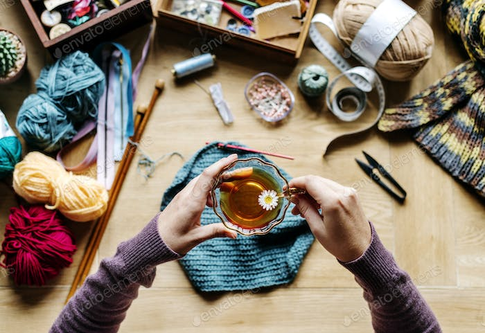 Aerial view of hands holding tea cup with knitting on wooden tab