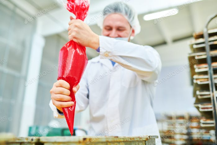 Confectioner using icing bag at factory