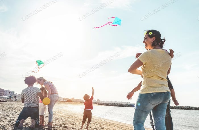 Happy families flying with kite and having fun on the beach