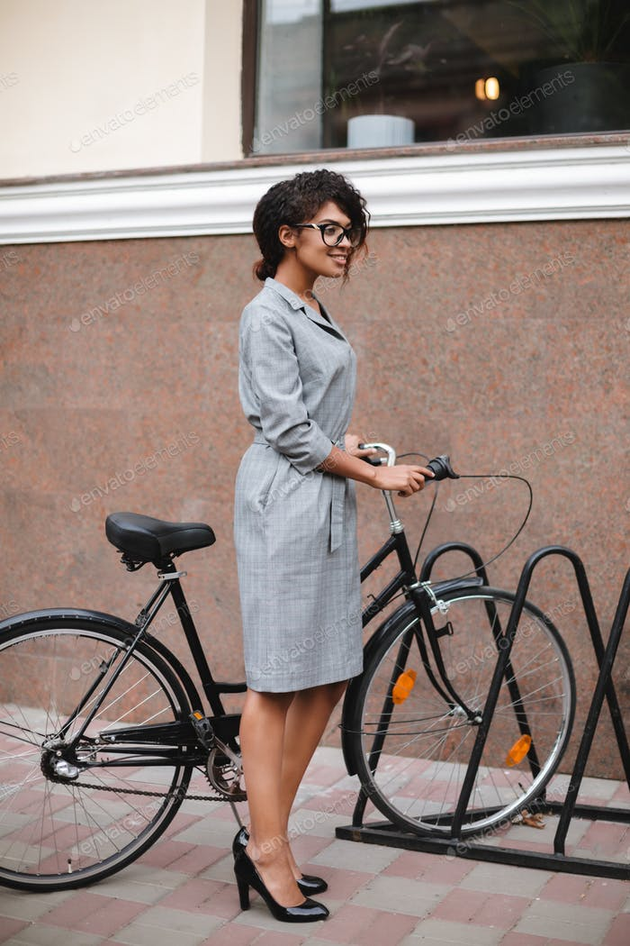Portrait of smiling African American girl in glasses standing with bicycle and happily looking aside