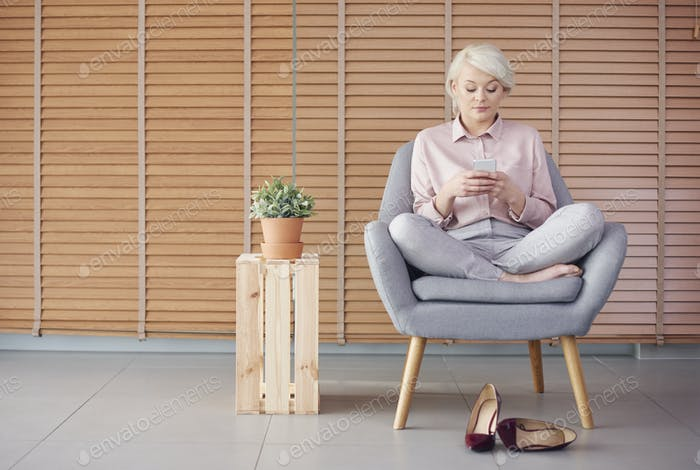 Smart woman sitting armchair and reading a text message