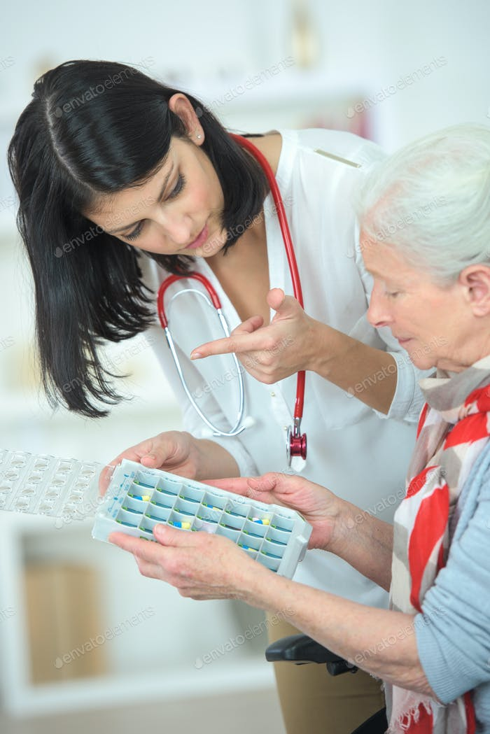 Nurse helping an old woman with her pill box