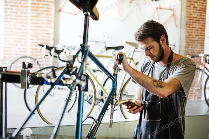 A man working in a bicycle repair shop pausing to check his messages.