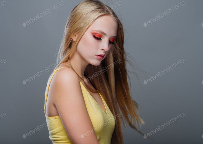 Woman with color make up and long blond hair teenager hipster beautiful girl