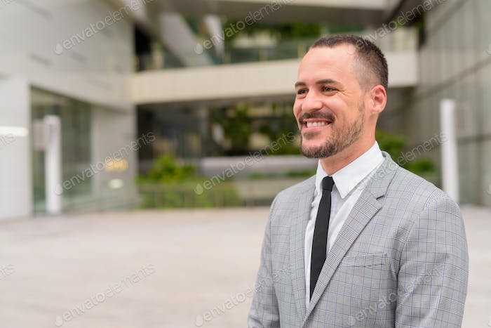 Happy Hispanic bald bearded businessman thinking in the city