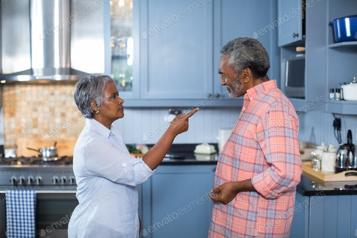 Side view of displeased couple standing in kitchen