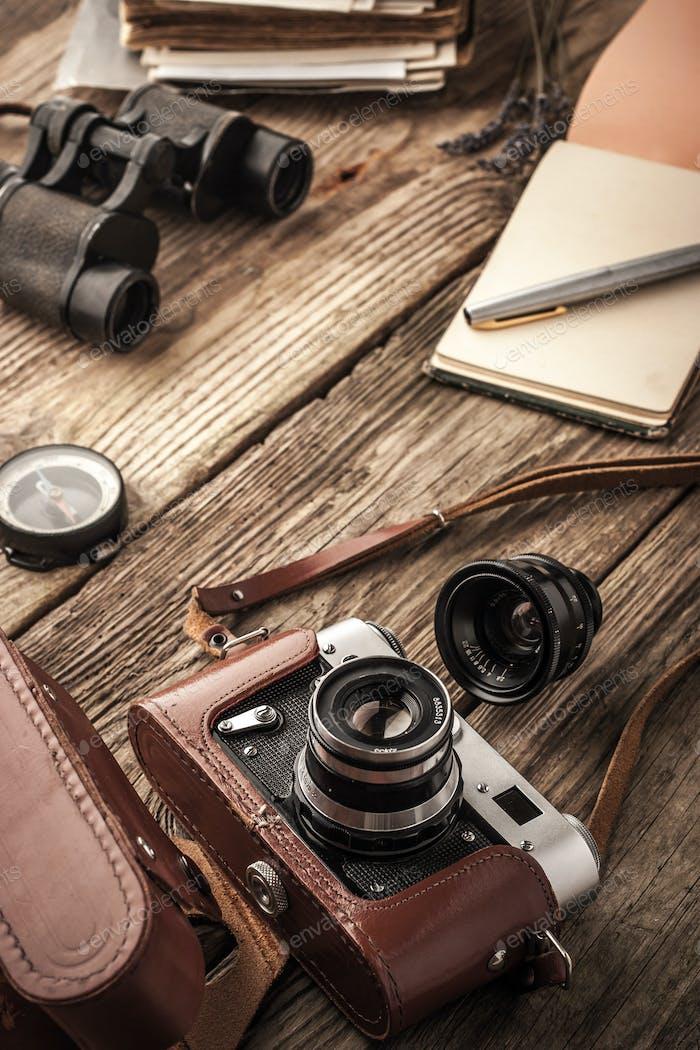 Kamera mit Notebook und Fernglas auf dem Holztisch vertikal