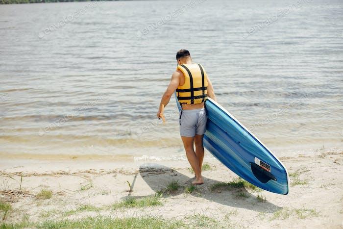 Sup Surfer an einem Sommerstrand
