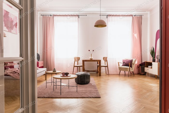 Pale pink living room interior in tenement house, real photo wit