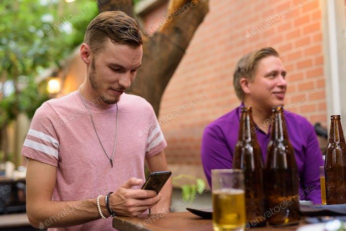 Glücklicher Mann sitzen und SMS im Freien während mit Bier
