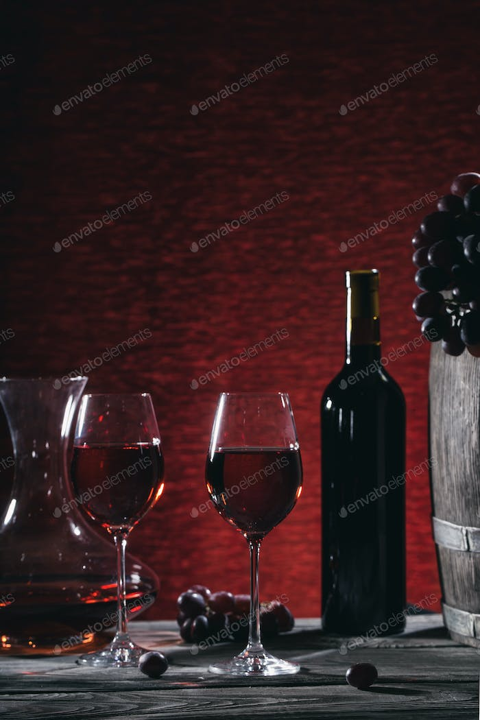 Wine still life with wine in glasses and grapes on a wooden tabl