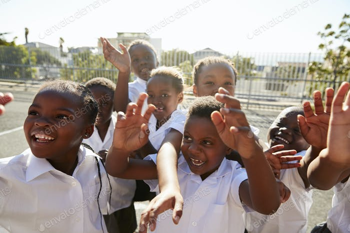 Elementary school kids in playground waving to camera
