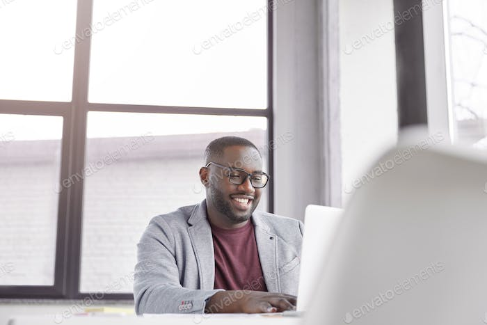 Glad black man manager keyboards on laptop computer, searches information about marketing agency. Po