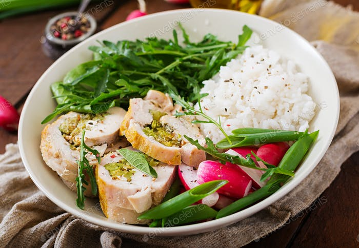 Healthy salad with chicken rolls, radishes, spinach,  arugula and rice.