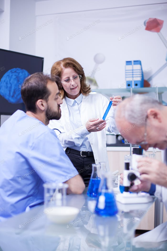 Medical professor working with microscope in the hospital laboratory