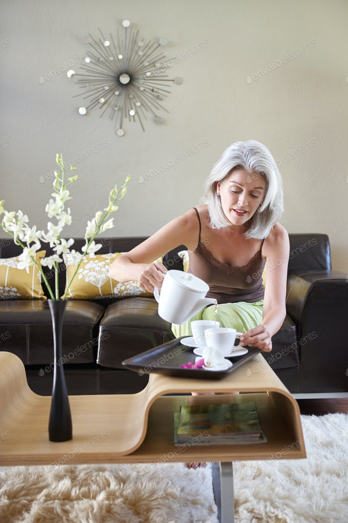 Woman pouring a cup of tea from a teapot