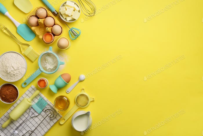Butter, sugar, flour, eggs, oil, spoon, rolling pin, brush, whisk, towel over yellow background