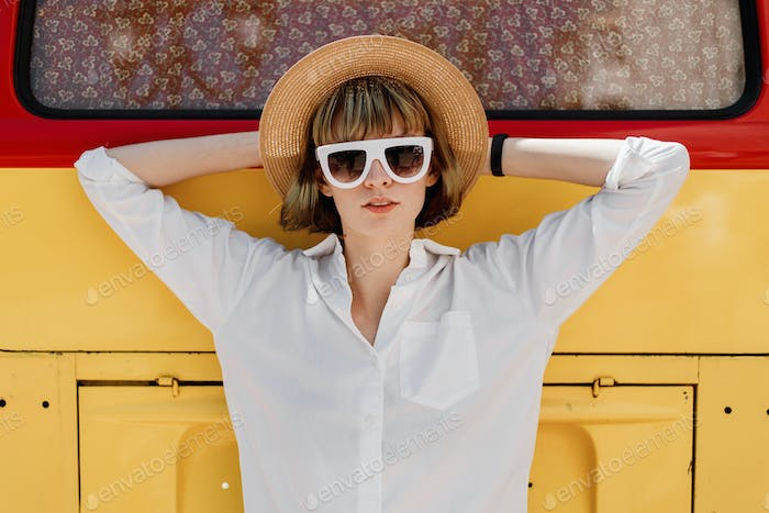 Stylish young woman in white sunglasses, a straw hat and white shirt poses next to the a bright red