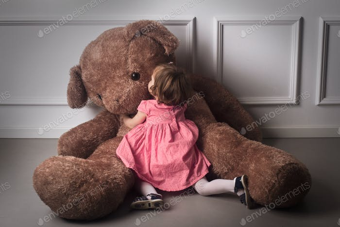 Little girl hugging a big teddy bear