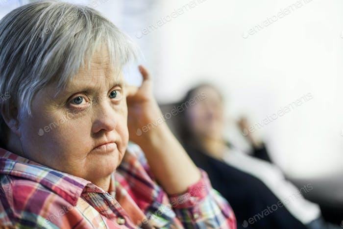 Вдумчивая женщина с синдромом Дауна отдыхает в доме престарелых