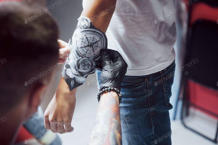 Татуировщик рисует рисунок для своего клиента