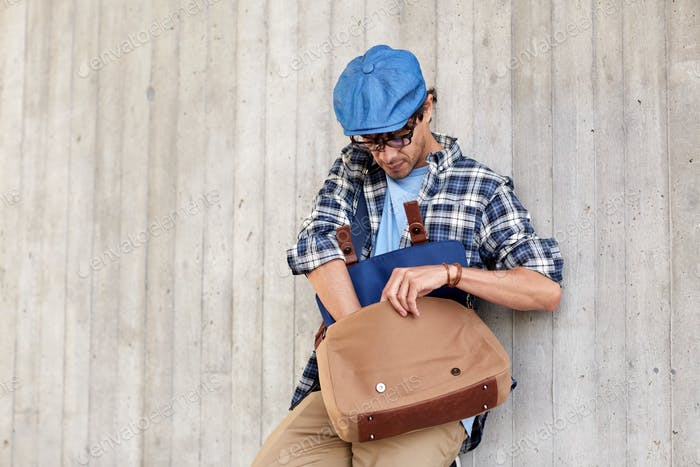 hipster man looking for something in his bag