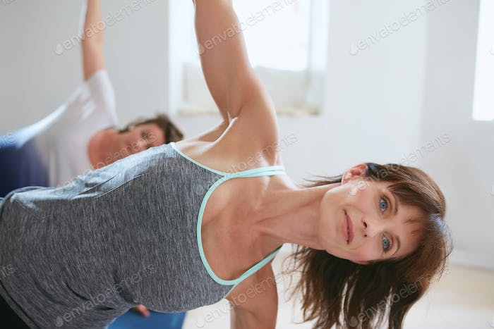 Mature woman doing stretches in a gym