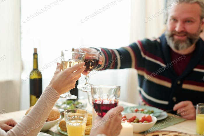Mature man and his daughter clinking with glasses of wine over snacks on table
