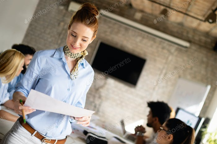 Beautiful businesswoman presenting to colleagues at a meeting