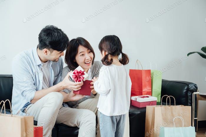 Little girl giving her parents surprising gift on festival day