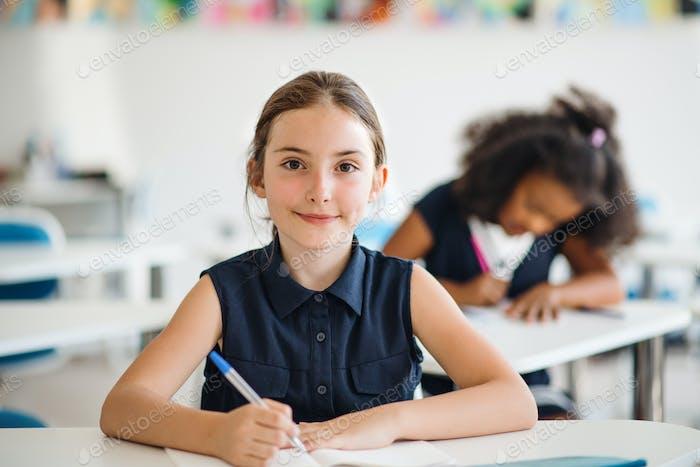 Ein kleines Schulmädchen sitzt am Schreibtisch im Klassenzimmer, Blick auf die Kamera
