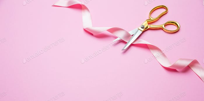Grand opening. Gold scissors cutting pink satin ribbon, pink background