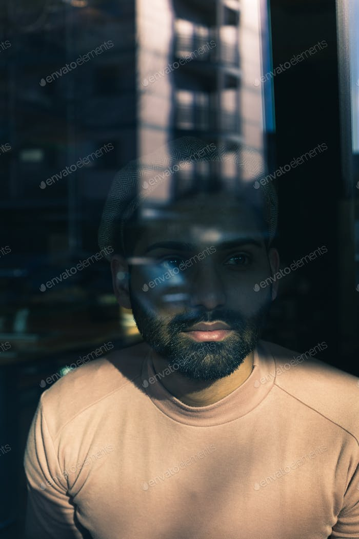 Portrait of an Indian man posing behind a glass