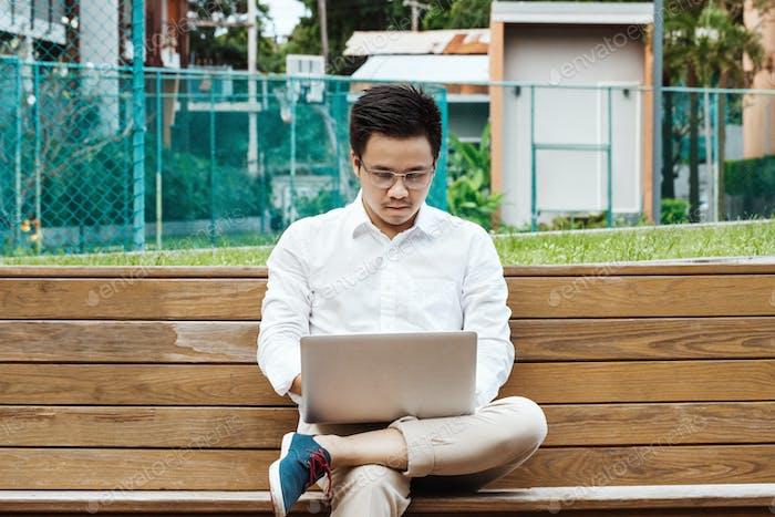 Молодой бизнесмен работает над ноутбуком в саду