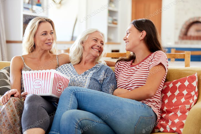 Mother With Adult Daughter And Teenage Granddaughter Eating Popcorn Watching Movie On Sofa At Home