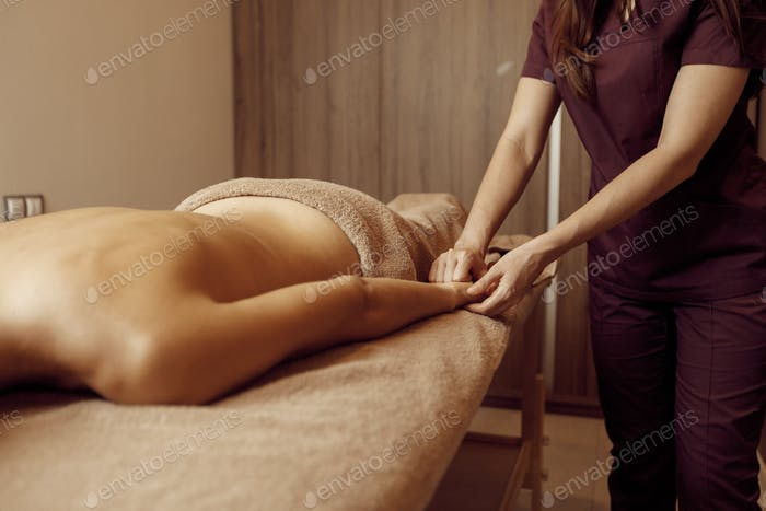 Female masseur pampering hands to young slim woman
