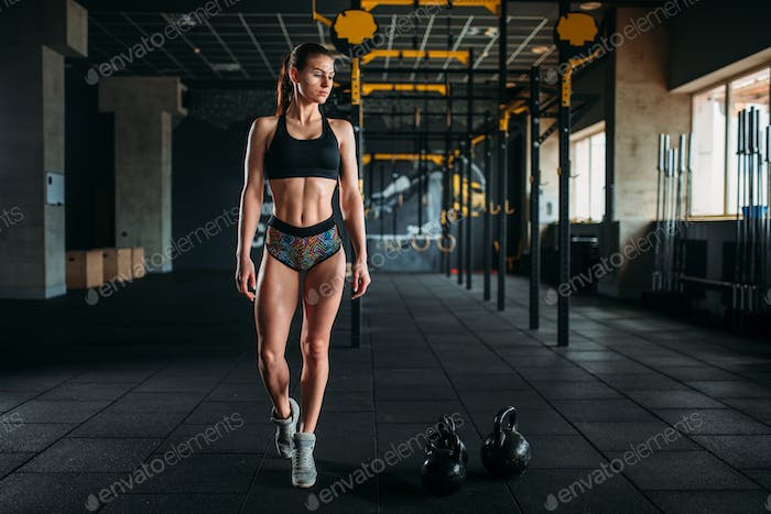 Female athlete with muscular body posing in gym