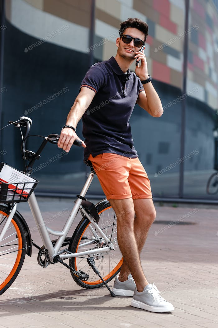 Stylish guy dressed in trendy casual clothes rides bicycle in the street against the background of a