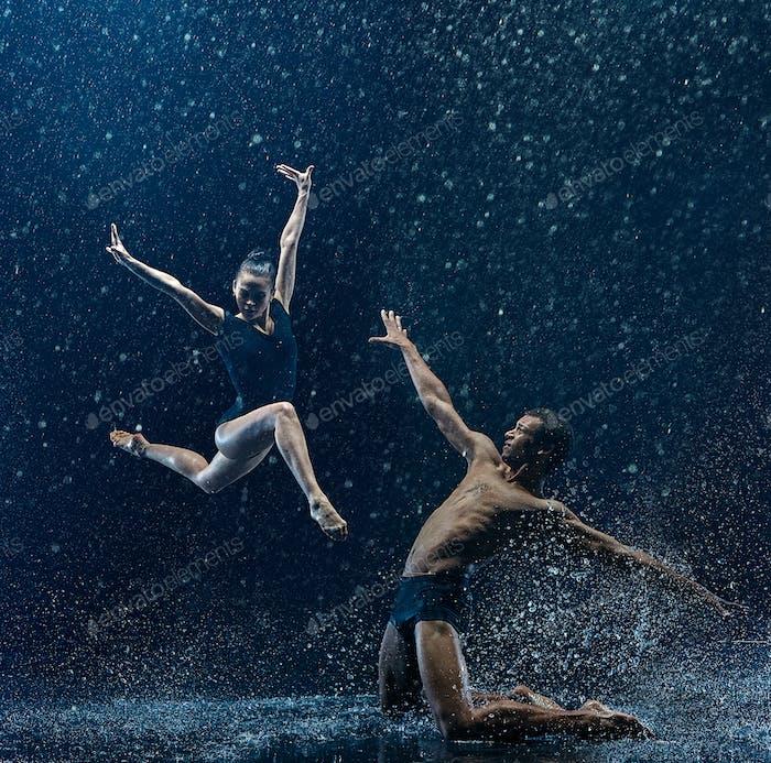 Joven pareja de bailarines de ballet bailando unde rwater gotas