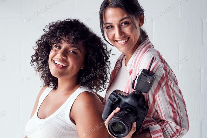 Portrait Of Smiling Female Photographer Holding Camera With Model In Studio Portrait Session
