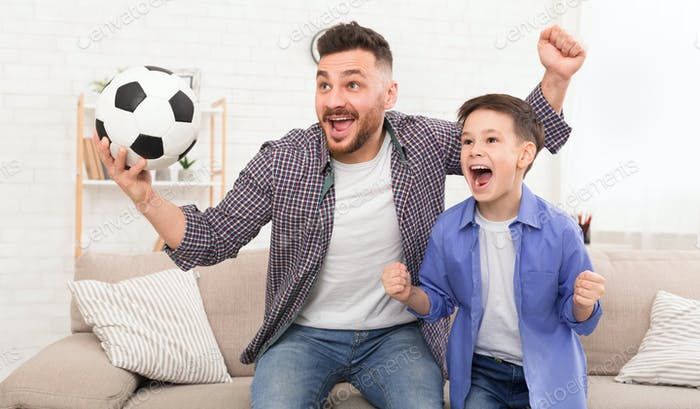 Emotional dad and son with football ball watching sport on tve