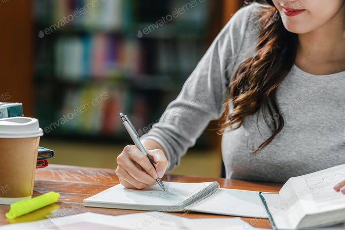 Closeup Asian young Student hand writing homework in library of university or colleage